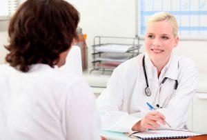 девушка врач принимает пациента